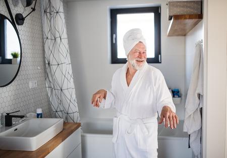 Homme senior faisant la routine du matin dans la salle de bain à l'intérieur à la maison.