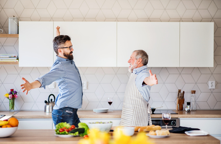 Adult hipster son and senior father indoors in kitchen at home, having fun.
