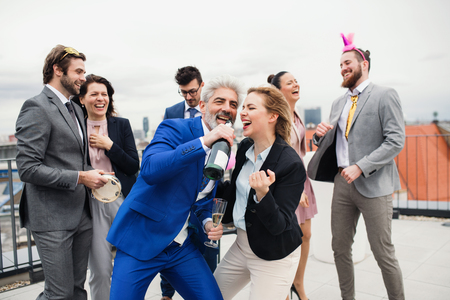 A group of joyful businesspeople having a party outdoors on roof terrace in city.