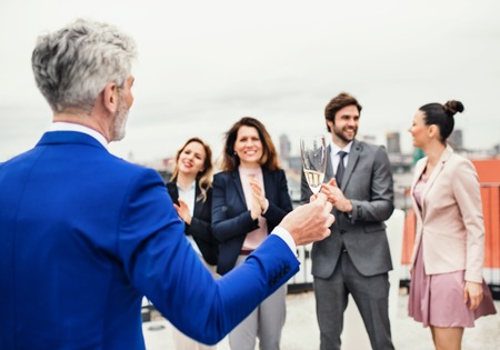A group of joyful businesspeople having a party outdoors on roof terrace in city. Standard-Bild - 123119262