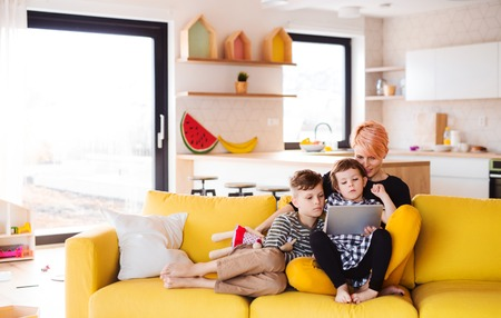 A young woman with two children indoors at home, using tablet. Stock Photo