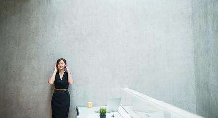 Junge Geschäftsfrau mit Kopfhörern, die gegen Betonmauer im Büro stehen.