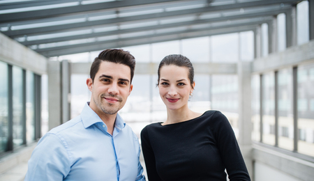 Two young architects standing in office, looking at camera. Imagens