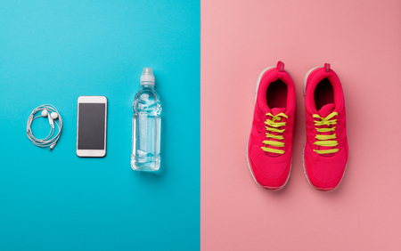 A studio shot of running shoes and smartpone on color background. Flat lay.