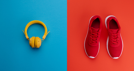 A studio shot of running shoes and heaphones on color background. Flat lay.