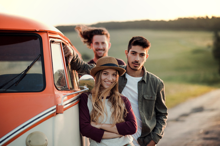 A group of young friends on a roadtrip through countryside, standing by a minivan.