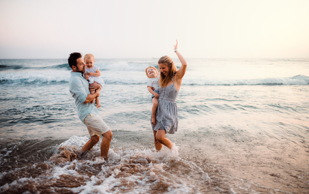 A young family with two toddler children having fun on beach on summer holiday.
