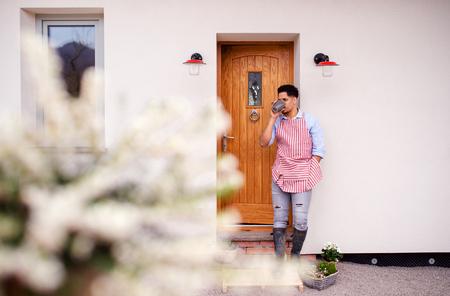 A portrait of young man gardener standing in front of door at home.