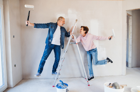 Senior couple painting walls in new home, having fun. Relocation concept. Foto de archivo