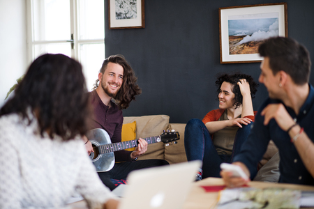 A group of young friends with guitar indoors at home, house sharing concept.
