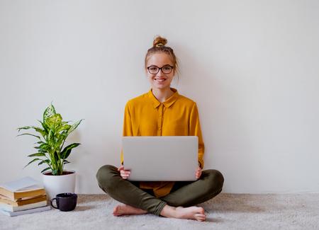 Eine junge Studentin, die beim Lernen auf dem Boden mit Laptop sitzt. Standard-Bild