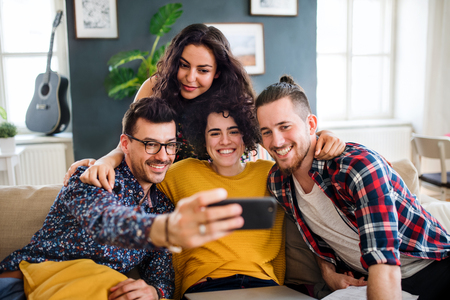A group of young friends with smartphone sitting on sofa indoors, taking selfie. Stock Photo