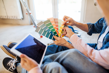 Sección media de la pareja de ancianos con muestra de color pintura nueva casa, concepto de reubicación. Foto de archivo