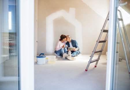 Senior couple painting walls in new home, kissing. Relocation concept.