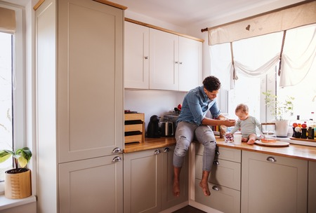 A father and a small toddler son eating fruit and yoghurt indoors at home.