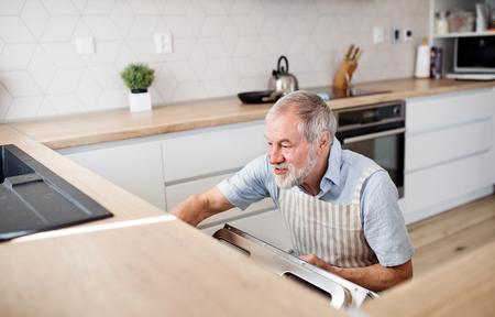 A senior man indoors in kitchen at home, loading dishwasher.