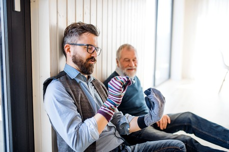 Portrait of adult hipster son and senior father sitting on floor indoors at home, having fun. Stock Photo