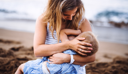 Young mother breasfeeding toddler daughter on beach on summer holiday. 版權商用圖片
