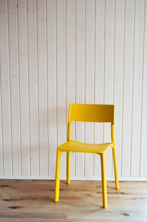 A plastic yellow chair against white wood texture background.