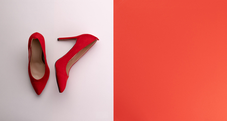 A studio shot of pair of high heel shoes on color background. Flat lay.
