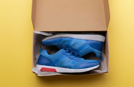 A studio shot of pair of running shoes in paper box. Flat lay.