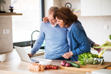 A portrait of senior couple with laptop indoors at home, cooking. Stock Photo