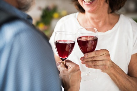 A midsection of senior couple in love indoors at home, clinking wine.