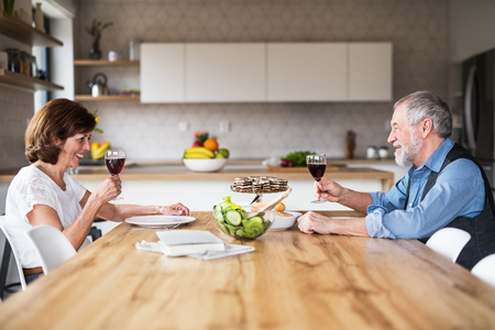 Senior couple in love having lunch indoors at home, talking.