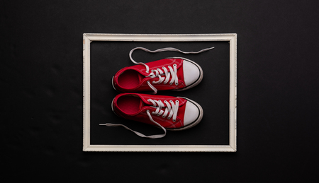 A studio shot of pair of canvas shoes on black background. Flat lay. 版權商用圖片