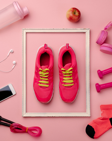 A studio shot of running shoes and other sport equipment on color background.