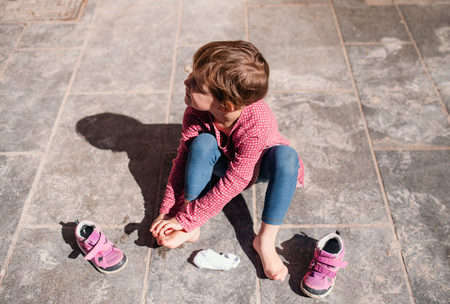 A top view of small girl sitting outdoors on pavement, taking off shoes. Imagens