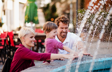 Parents with two small daugther having fun outdoors in town. Фото со стока
