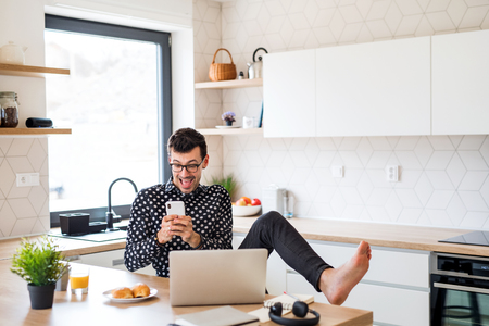 Young man with smartphone and laptop, eating breakfast indoors at home.