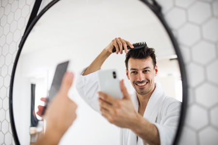 Young man combing hair in the bathroom in the morning, taking selfie.