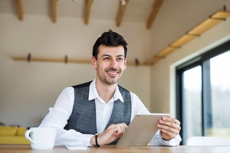 Young man with coffee sitting at the table, using tablet. Stock Photo