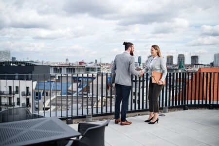 Two young business people standing on a terrace outside office, shaking hands. Imagens