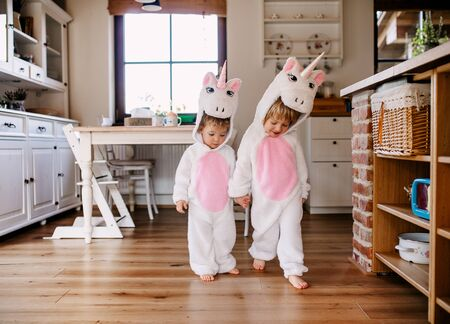 Two toddler children with unicorn masks walking indoors at home.