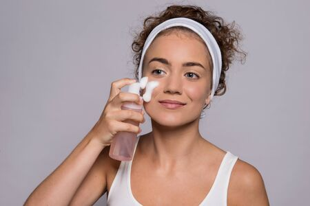 Portrait of a young woman cleaning face in a studio, beauty and skin care. Stock Photo - 124677194