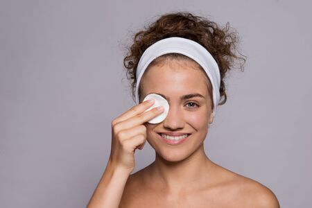 A portrait of a young woman cleaning face in a studio, beauty and skin care. Stock Photo