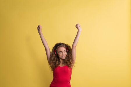 Portrait of a young woman with headphones in a studio on a yellow background. Stock Photo - 124677236