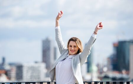 A young businesswoman standing on a terrace, expressing excitement.