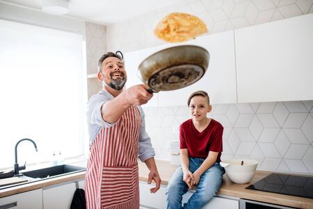 Mature father with small son indoors in kitchen, flipping pancakes. 스톡 콘텐츠 - 124677270