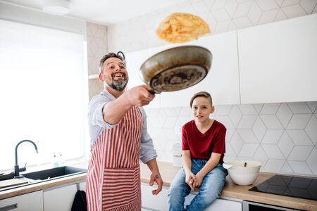 Père mature avec petit fils à l'intérieur dans la cuisine, retournant des crêpes. Banque d'images