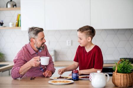 Mature father with small son indoors sitting at the table, making pancakes.
