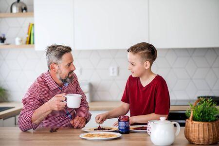 Padre maduro con un hijo pequeño en el interior sentado a la mesa, haciendo panqueques.
