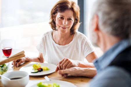 Senior couple in love having lunch indoors at home, holding hands. Stock Photo