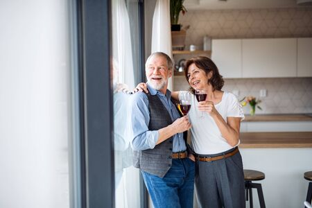 A senior couple with wine indoors at home, looking out of window. Stock Photo - 124677287