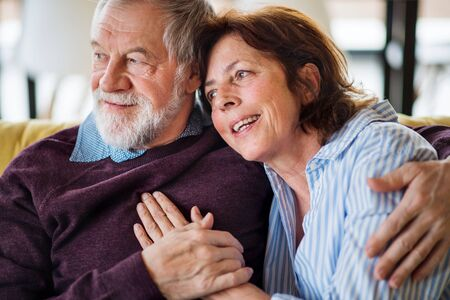 An affectionate senior couple in love sitting on sofa indoors at home. Stock Photo