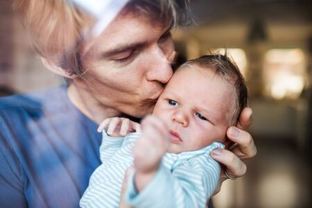 A young father holding a newborn baby at home, kissing.