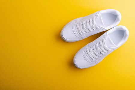 A studio shot of white running shoes on yellow background. Flat lay.